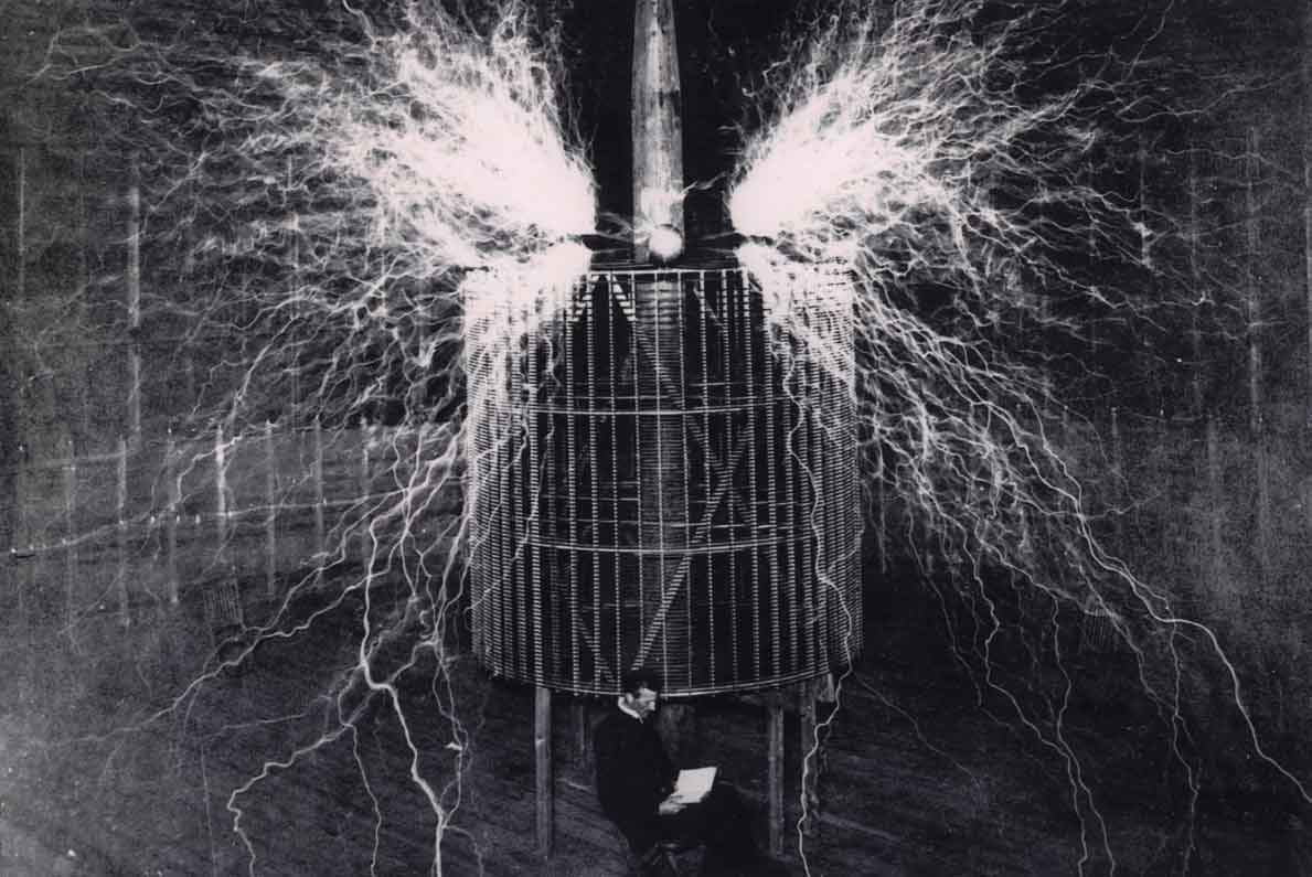 Tesla photographs tesla in colorado springs laboratory 1899 seated in front of the operating transformer sciox Gallery